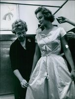 A woman assisting Princess Kira of Prussia try on a dress. 1960.