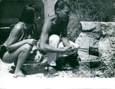 Man holding something and woman sitting beside.  Photo taken Aug.26,1963