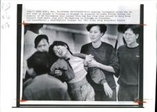 Prison officers in black tracksults take a weeping vietnamese woman to a ferry.