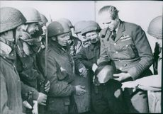 Soldier standing, holding a helmet in his hands, other soldiers gathered around him looking at him and smiling.