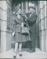 Maurice Auguste Chevalier standing with a woman.