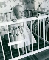 Prince Jacques duke of Orleans while still a cute baby, standing and smiling inside his cage.