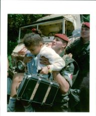 Rwanda war:a french paratroopers helps an undentified child onto a truck.