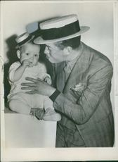 Maurice Chevalier playing with a child.
