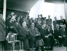 People sitting together, one of them looking towards camera.