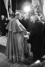 Pope Paul VI shaking hands with unknown man.
