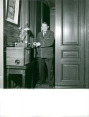 Rene Coty standing at doorway.