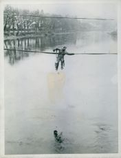 U.S. SIGNAL CORPS MAN SWINGS OVER MOSELLE RIVER
