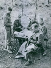 British soldiers playing cards while the other one sews on a button during their free time. 1940.
