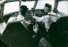 A photo of a pilot and his co pilot siting and operating the airplane during take off.