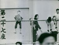 Kids in fence while the other playing in the ground in Hong Kong, 1967.