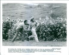 "Bill Harding (Bill Paxton and Jo Harding (Helen Hunt) run from an oncoming tornado in ""Twister""."