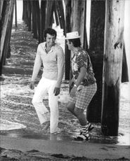 Herb Alpert talking and smiling with a man in the shore, 1969.
