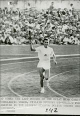 Giancarlo Peris runs into stage with the Olympic torch