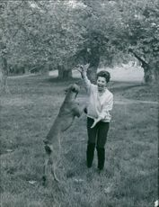 Giorgia Moll standing and playing with a dog.