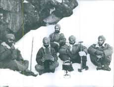 Indian soldiers sitting on the ice, having tea together in Himalaya.