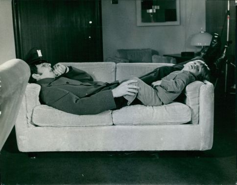 Man and a child lying on couch.