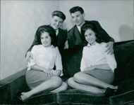 Boys and girls sitting and smiling together in a picture pose.  1963