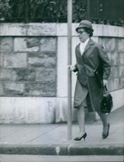 A photo of a woman running on the street. 1963