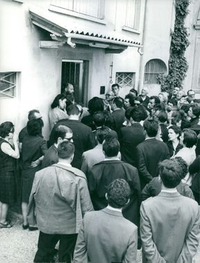 PEOPLE GATHERED IN FRONT OF A HOUSE