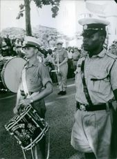 Soldiers playing musical instruments during an event. 1964