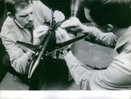 Men Siting and assembling a model of airplane.