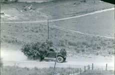 A camouflage truck passing though the road in the village.
