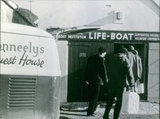 People getting into the life boat holding huge cans in their hands. 1966