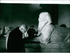 A man admiring Egyptian sculpture.