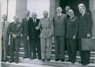Bernard Montgomery standing with other people in front of the building.
