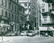 A photograph of a road and a shop during a chaotic day.  Taken - Circa 1962