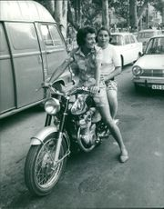 Marielle Goitschel with Annie Lois sitting riding a motorbike.