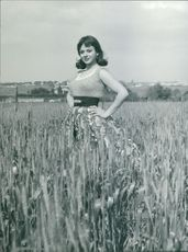 Sandra Milo standing in the farmland, posing.
