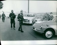 Soldiers approaching towards a car.