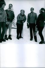 Queen Juliana, Princess Margriet, and Princess Irene with their husband, Pieter  van Vollenhoven and Carlos Hugo talking together in the snowy fields, 1970.