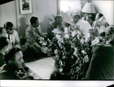 Men in a room with flowers having a conversation in Laos. June 19, 1961.