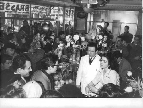 Jacques Charrier with a woman, surrounded by press reporters.