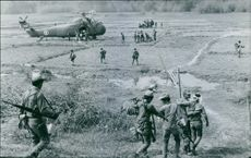 Soldiers moving towards the helicopter while communicating with each other.