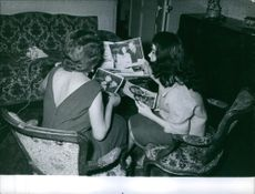 Jacqueline Boyer siting with a woman and looking at photographs.