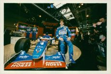 Damon Hill posing with his racing car during Yamaha automobile F1.