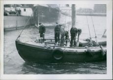 People in boat, standing together and communicating with each other. 1940