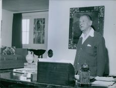 William Somerset Maugham is standing behind a table looking at something.