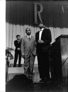 Ray Charles Robinson laughing standing on the stage in a ceremony.