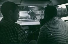 Men siting inside of the car and looking policemen outside while talking to someone on radio.