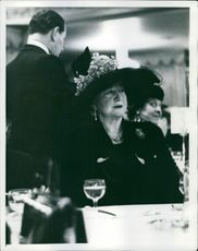 Mrs. Evelyn Nash sitting and looking at something during an event.