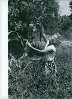 Lilian Harvey looking at the plant. 1960.