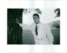 Photo of a guy wearing a white suit and leaning on a tree.