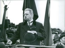 Photo of Hjalmar Branting standing and holding his hat in front of many people.