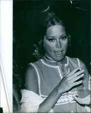 Mary Tyler Moore is in a conversation while holding a glass of juice in a dinner attended.