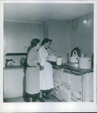"""Danish housewives pouring hot water into a kettle.  """"Danish refugees, Housewives Danish refugees in Tureberg.""""  1944"""